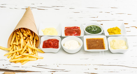 French fries on a piece of crafted paper with different sauces in white sausers on the white wooden background with cracking paint