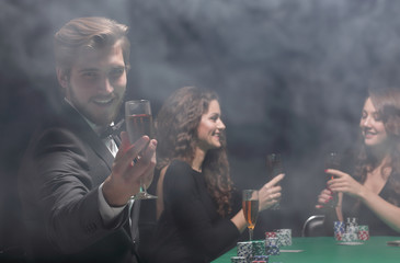 happy group of people celebrating a successful game of poker