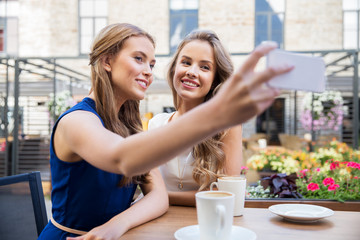technology, lifestyle and people concept - happy young women taking selfie by smartphone and drinking coffee at cafe outdoors