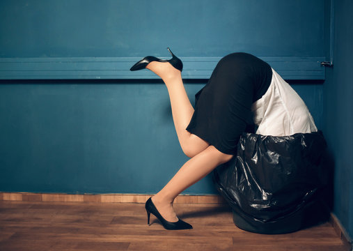 Woman trying to get her head out of garbage basket. Lady dressed in business casual clothes got her head stuck in black trash can.