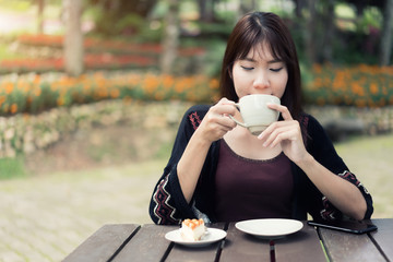 Asian Women relaxing at home garden with cup of coffee and feeling refresh.