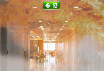 double exposure green emergency exit sign in hospital showing the way to escape with fire