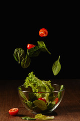 Tomatoes and salad leaves falling in bowl above wooden table surface