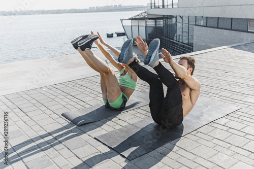 9c241d2e726d Fit fitness woman and man doing fitness exercises outdoors at city ...