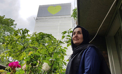 Zainab Jafari,  who's father-in-law, Ali Yawar Jafari, lived on the 11th floor of Grenfell Tower and died in last year's fire, poses for a photograph on her balcony on the Lancaster Estate, in North Kensington, which overlooks the Grenfell Tower, in London