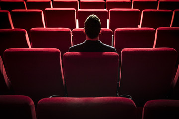 portrait of handsome young man alone at the cinema, sitting alone at the cinema