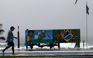 A man walks next to graffiti depicting the Brazilian player Neymar, at Barra da Tijuca beach before the opening ceremony and first match of the FIFA World Cup, in Rio de Janeiro