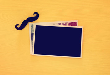 top view of blank photo frames on yellow wooden background.