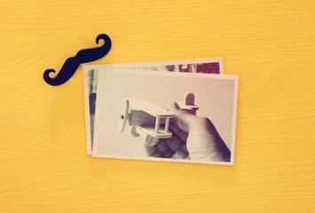 top view of photo collage on yellow wooden background. vintage filtered image.