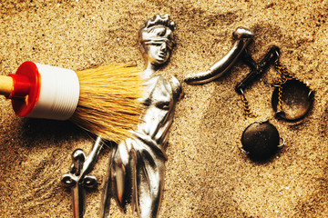 Discovering Justice figure in sand during police forensic investigation