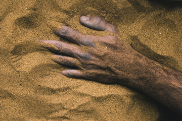 Hand of dead person buried in sand