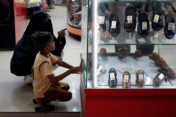 A mother and child sit in front of a showcase while selecting sandals ahead of Eid al-Fitr, which marks the end of the holy fasting month of Ramadan, at a market in Karachi,