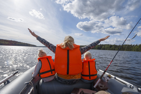 Girl in a life jacket floating on the boat with his hands up. Children in life jackets sitting next