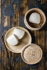 Empty gua bao steamed buns in ceramic plate and opened bamboo steamer over dark wooden plank background. Flat lay, space. Asian fast food.