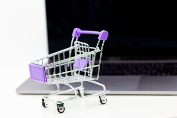 Shopping cart for retail business on notebook. Image use for online and offline shopping, marketing place world wide.