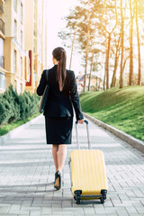 Beautiful young business woman in a suit and in shoes walking on a city street with yellow travel bag