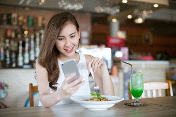 Young Asia woman eating spaghetti at restaurant and using smart phone
