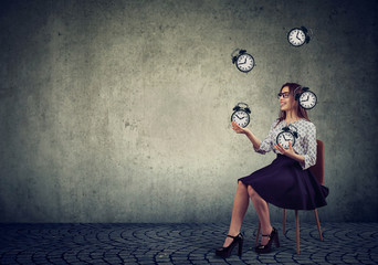 Woman juggling with alarm clocks