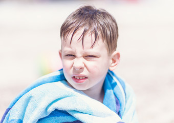 Young boy sitting on the beach with towel. Family vacation or holiday concept.