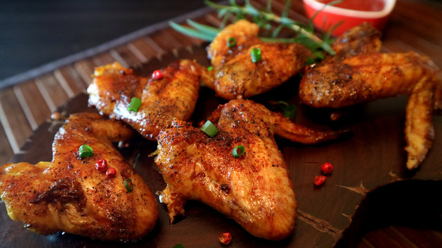 Rosted chicken wings and sauce on wooden background.
