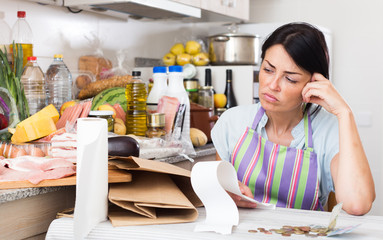 Woman is unpleasantly surprised of price in the check after shopping in grocery market