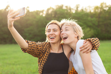 Two cheerful young women are making selfie on mobile phone