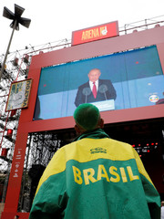 A soccer fan watches in a big screen the opening ceremony of the FIFA World Cup in downtown Sao Paulo