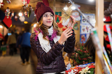 Glad young girl buying xmas gifts