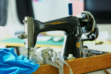 Retro sewing machine on designer clothes desktop