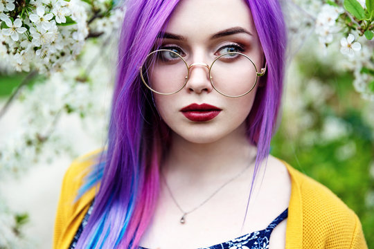 Hipster girl with colored hair in glasses. Woman model purple and blue hair. Teenager against the background of cherry blossoms. White skin. Ultra Violet hair