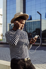 Black man in headphones using smartphone