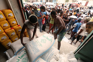Workers unload sacks of wheat flour as people gather outside an aid distribution centre in the Red Sea port city of Hodeidah