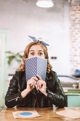 Pretty lady in leather jacket sitting at the table and amazedly looking in camera while covering her face with notebook in cafe