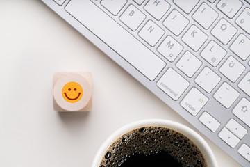 Würfel mit lächelndem Smiley am Arbeitsplatz