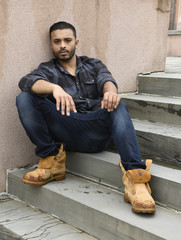 young man sitting on steps outside