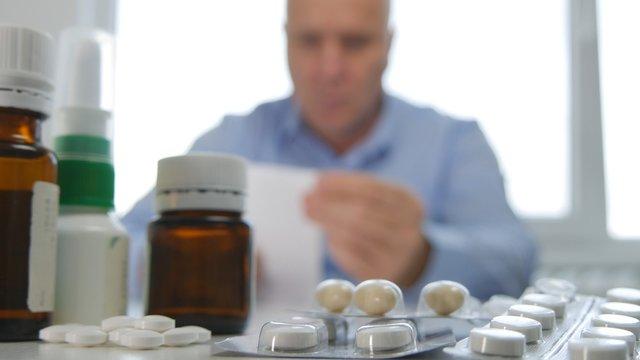 Man With Many Pills on the Table Looking to a Medical Prescription