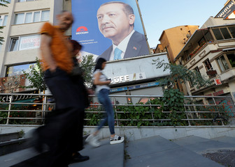 People walk past an election poster for Turkey's President Tayyip Erdogan in Istanbul