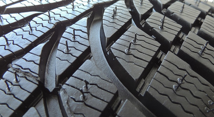 Rubber surface of new car tire with sipes and grooves close up