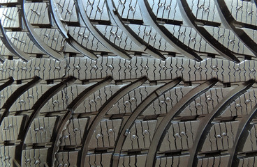 Tread area of new modern car tire with blocks and ribs close up
