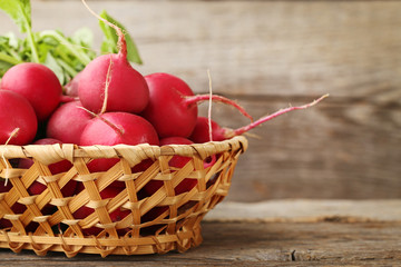 Red radishes in basket on grey wooden table