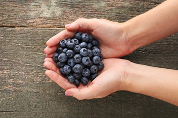 Female hands holding ripe and sweet blueberries