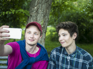 portrait of two young smiling handsome brothers outdoors doing a selfie with phone in the park