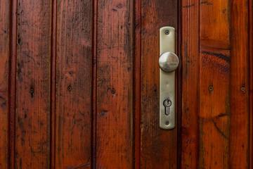 door handle knob on red wooden door background texture with empty space for copy or text