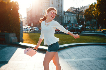 Young excited woman wearing stylish outfit outdoors. Happy girl jumping and having fun. Beauty fashion concept
