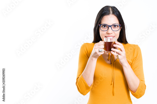 fb2b91cb663baa Beautiful brunette woman holding transparent cup with tea bag looking at  camera feeling the aroma -