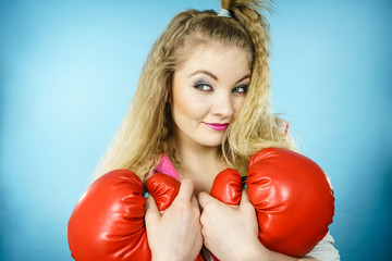Funny girl with red gloves playing sports boxing