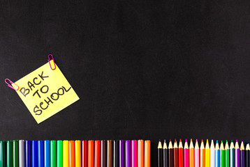 Back to school background with a lot of colorful felt-tip pens and colorful pencils, titles Back to school on the yellow piece of paper or sticker on the black scratched chalkboard