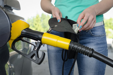 Lack of money for gasoline and fuel. Expensive gasoline. Women driver showing a one dollar and empty wallet against the background of a fuel nozzle in the gas tank. Increase in gasoline prices.