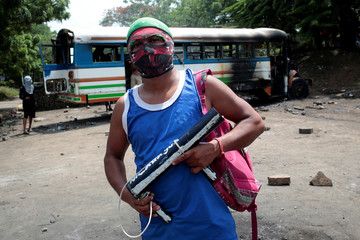 A protester stands in front of a burned bus during a protest against Nicaragua's President Daniel Ortega's government in Tipitapa