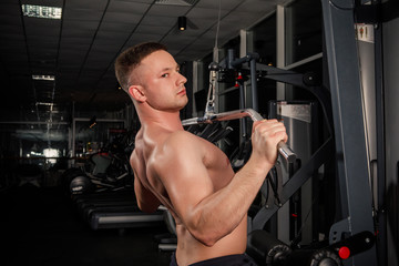 young male athlete bodybuilding in blue sportswear doing exercises with dumbbells in a dark gym